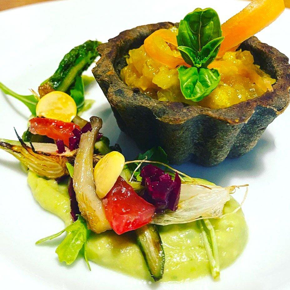 Crostata salata di lenticchie con mostarda piccante di pere, letto di crema di avocado e insalatina di verdure grigliate